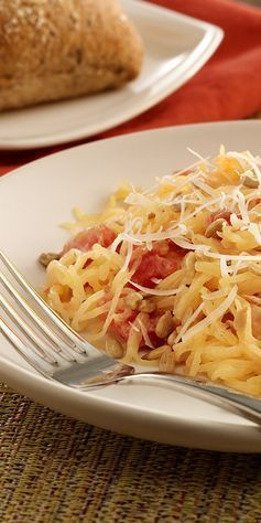 Spaghetti squash recipe with tomatoes in a cheesy sauce finished with Parmesan cheese and crunchy sunflower kernels.