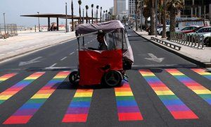 People cross a rainbow-coloured pedestrian crossing before the Tel Aviv gay pride parade