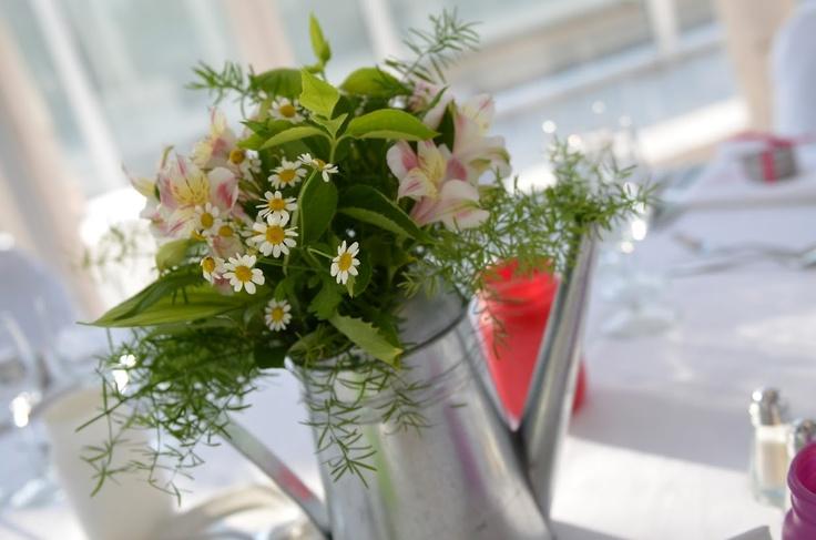 Des arrosoirs fleuris comme centres de table