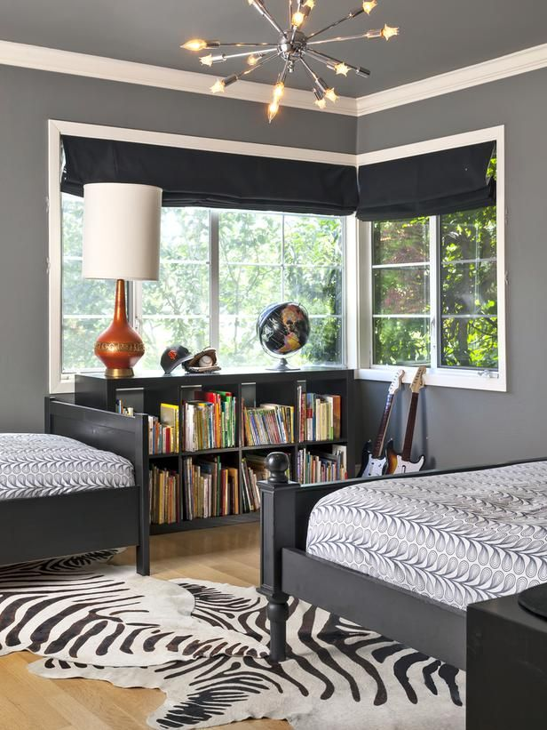 """Black and white even works well in a kids' room — creating the perfect backdrop for bright toys, books and accessories. Here, designer Holly Bender of Holly Bender Interiors chose a black-and-white zebra rug to create movement in a room that boasts rich, gray walls. """"I love deep shades of gray like Benjamin Moore's Chelsea Gray. It provides a warm, yet modern, feel and really pops against white trim,"""" says Bender."""