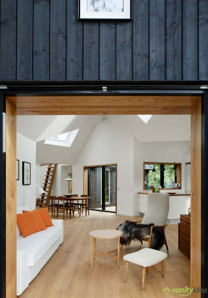 the interior walls reveal the contrast with the black facades of the house, while the large windows allow natural light to spread throughout the entire home.