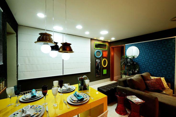Molduras coloridas, parede preta, ambiente colorido, mesa amarela