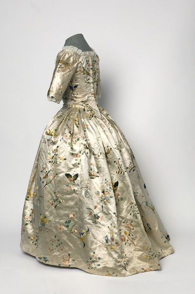 1760 side view of  girl's dress, a back-fastening gown with a trained skirt. Made of ivory silk hand embroidered in colored silks with floral motifs, birds, butterflies, and baskets of fruits and flowers.