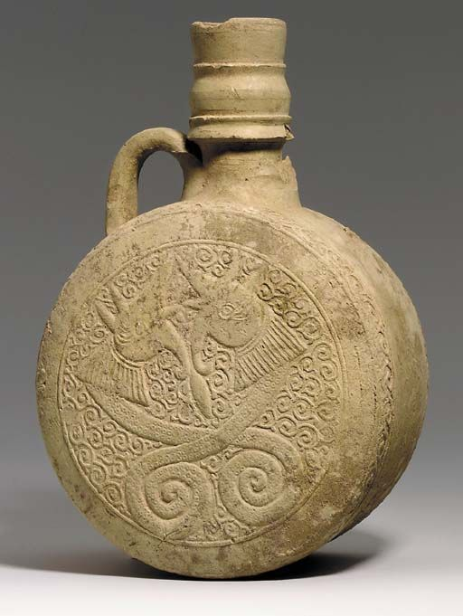 A MAMLUK UNGLAZED POTTERY PILGRIM FLASK SYRIA, 13TH CENTURY  Of cylindrical form with slightly convex faces each moulded with fine scrolling tendrils flanking confronted dragons with entwined tails, a band of spiralling vine around each edge, the mouth moulded with simple bands, two simple handles at the shoulders, one handle missing 11¾in. (29.8cm.) high