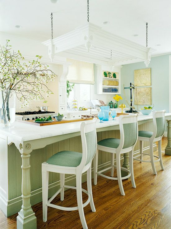 """For this kitchen, cleverly mixing elements from two semi-custom cabinetry collections--""""Edwardian"""" and """"Victorian""""--created a gracious, centuries-old look. Furniture-style details include a gently arched apron beneath the countertop, turned legs set atop plinth blocks, and an ornate potrack topped with crown molding."""