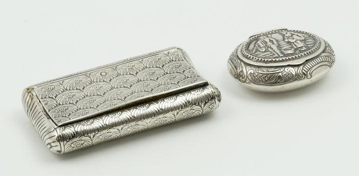 Een concaaf gebogen zilveren tabaksdoosje met decor van gestyleerde chrysanten, l. 8 cm (hoekjes gedeukt) en een ovaal zilveren snuifdoosje met decor van boeren in landschap, Herman Hooijkaas, Schoonhoven 1906-1924