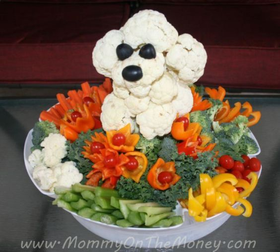 Fruit and Vegetable Choppers help to make this vegetable poodle that is made from raw cauliflower with black olives for eyes and the nose. Around the are chopped vegetables artfully arranged. Very effective.