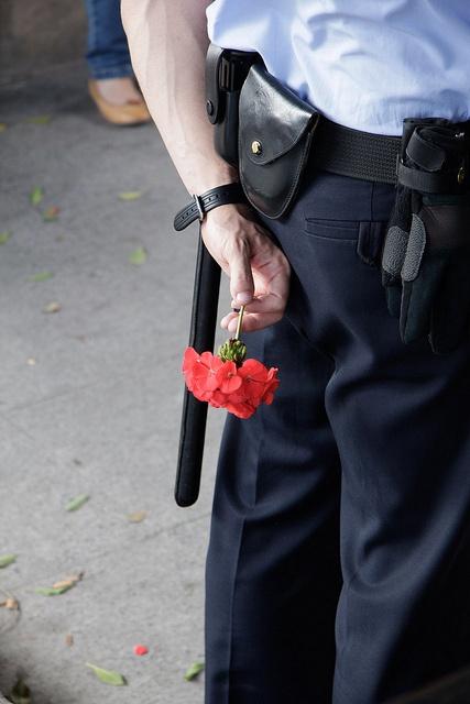 Mediodía 20/05/2011  Un policia municipal encargado de la vigilancia sostiene una flor en La Glorieta, lugar de la acampada de indignados de Murcia.