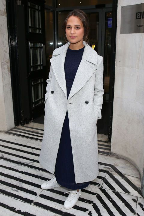 21 October Alicia Vikander teamed her midi dress with a pair of boxfresh white trainers and a chic Club Monaco coat for an early morning apperance on BBC Radio 1.