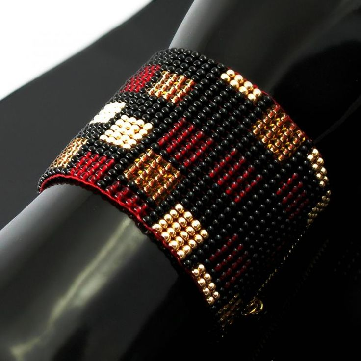 Wide, bold, slinky and feeling so good worn ... this cuff was made on a bead loom using seed beads. On a black background you find rectangles of a dark red which seems to light up in the right angle of light, a sand color which reminds of liquid honey and a bold metallic gold.