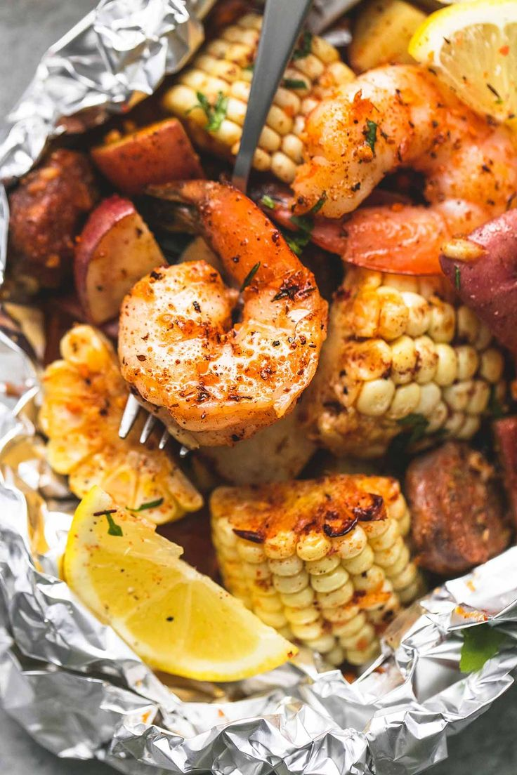 Shrimp boil foil packs baked or grilled with summer veggies, homemade seasoning, fresh lemon, and brown butter sauce.