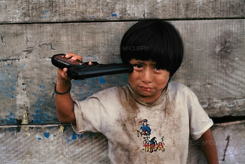 Young boy holds a toy pistol to his head, Alto Churumazu, Yanesha, Peru, 2004, Magnum Photos      Young boy holds a toy pistol to his head, Alto Churumazu, Yanesha, Peru, 2004. Published by Magnum Photos.
