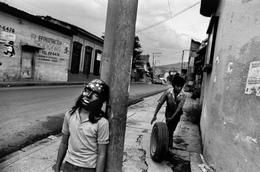 """Larry Towell, EL SALVADOR. San Salvador. Child with star mask during """"Day Of The Dead."""" Other child in background rolls tire for repair in garage where he works at an adult's job. 1992."""