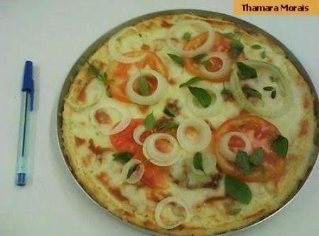 Receita de pizza de arroz - 2 xícaras de arroz cru, 1 xícara de leite, 8 colheres (sopa) de óleo, 3 ovos, 1/2 xícara de queijo parmesão ralado, 1 colher (sopa) de fermento químico em pó, 1 tomate médio, 300 g de queijo muçarela, 1 cebola pequena, 1/2 molho de manjericão