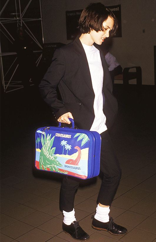 winona ryder in the 90's. black and white. White socks and dinosaur luggage from Sanrio!