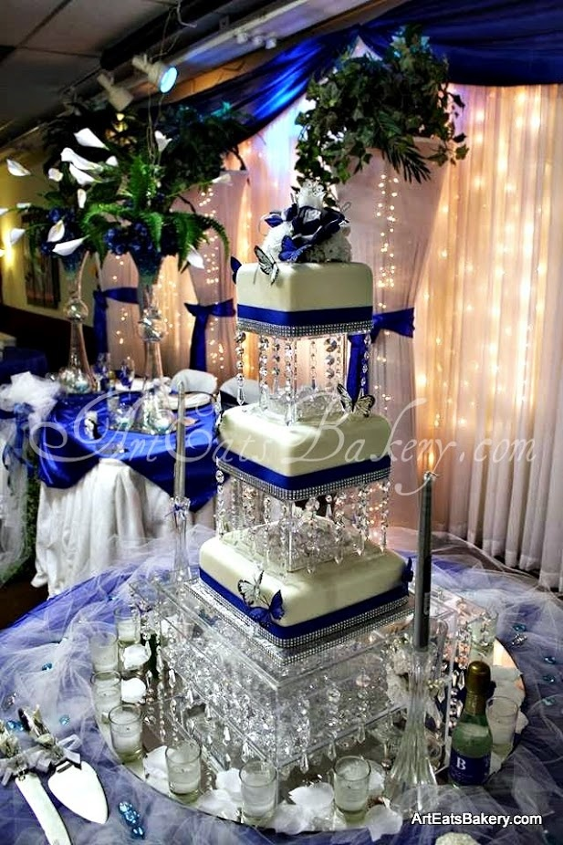 Three tier square modern wedding cake with royal blue ribbons, sugar butterflies, rhinestones and crystal cake stand.