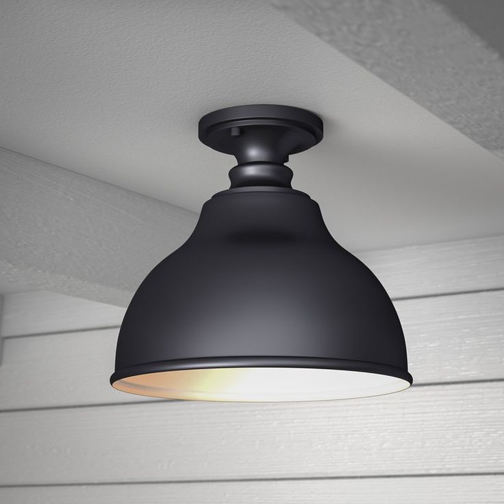 Industrial design meets modern farmhouse style in this charismatic one-light outdoor semi flush mount. Featuring a charming bell shade in a matte black finish, this weather-resistant design showcases simple moldings and a bright white interior. Establish a pastoral aesthetic on your front porch by rolling out an all-weather buffalo-check runner for a pleasant pop of pattern, then place a wrought iron end table with a latticework tabletop between two rustic spindle-back rocking chairs for an…