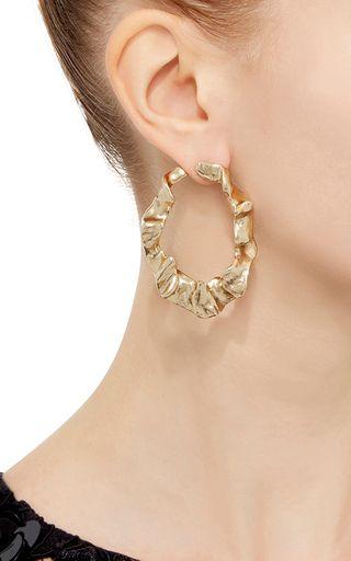 These **Oscar de la Renta** earrings feature a flounced brass design in a semi-closed hoop design.