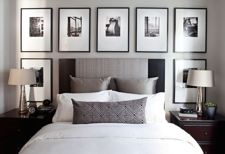 Chic bedroom with black and white photos in gallery frames over black linen headboard accented with platinum gray pillows and diamond pattern lumbar pillow flanked by tapered antique mercury lamps on traditional nightstands.