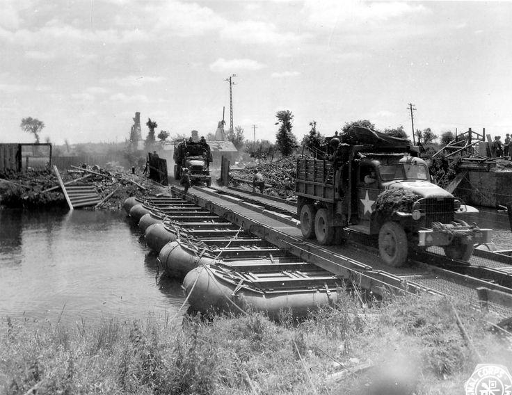 https://flic.kr/p/goDe9T   p013055   Le Génie US a installé un pont flottant Steel Treadway Bridge M1 ou M2 sur un cours d'eau. Deux GI's à l'entrée du pont. Le premier  GMC est un CCKW 352 SWB avec affut M37, il fait partie d'une des unités de l'Ordnance Co Aviation, de la IX Air Force, à l'arrière du camion un soldat armé. Derrière un GMC CCKW 353 LWB benne Génie avec affut M36,  unité ? En arrière plan une maison en ruine, sur la droite des GI's à côté d'une porte belge. Selon ce site…