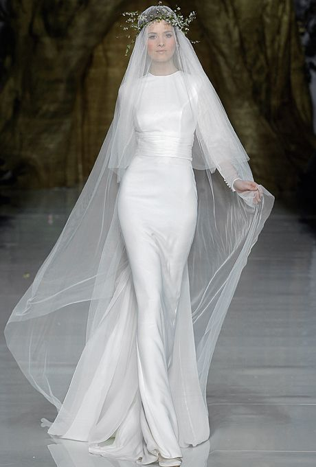 "Brides.com: . ""Yelice"" silk crepe sheath wedding dress with a high neckline, long sleeves, and banded waist, Pronovias"
