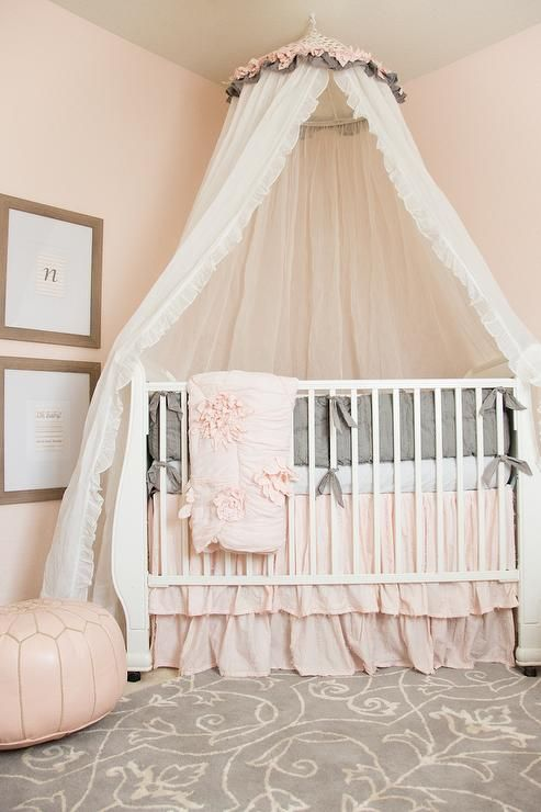 Gorgeous pink and gray nursery features two wood framed typography prints mounted on light pink walls highlighting a white tulle canopy hanging over a white crib dressed with a baby pink bed skirt, white sheets and a gray bumper accented with an adorable pink throw blanket as a pink Moroccan leather pouf its beside the crib on a gray and white printed rug.
