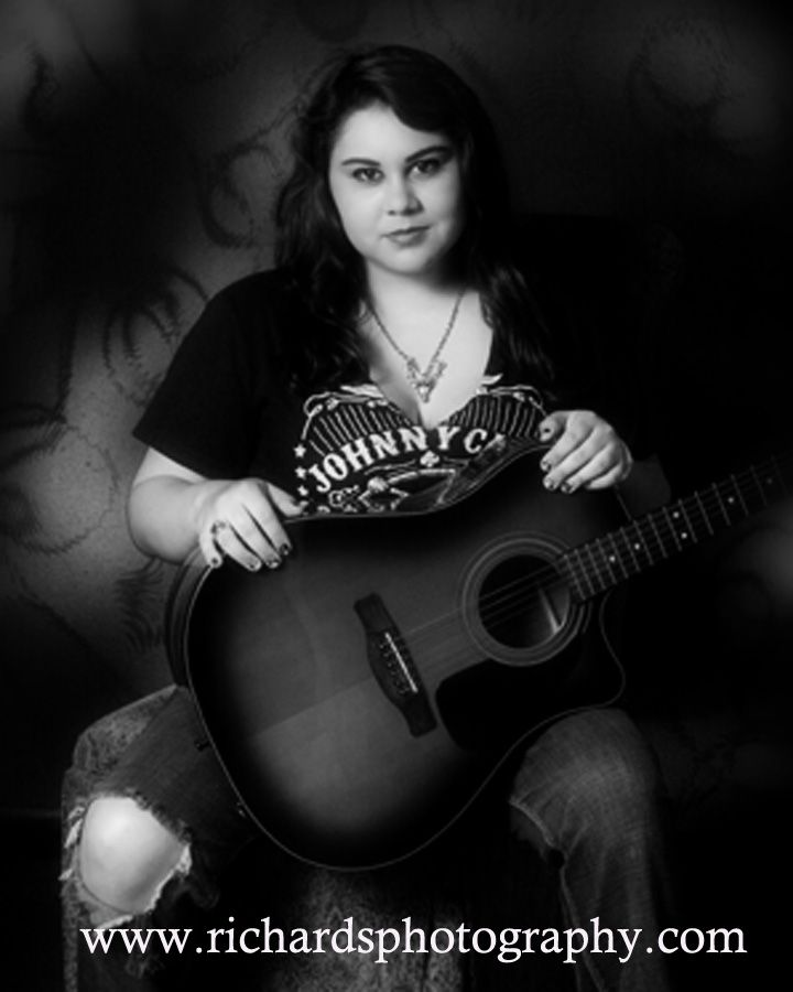 Black and white high school senior with guitar in her arms.