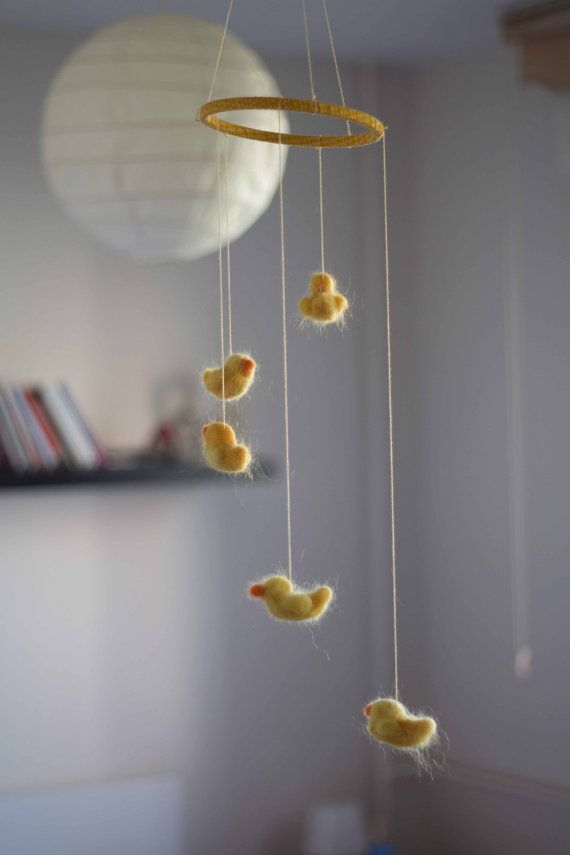 All the cute ducklings are needle felted by me of a %100 wool and strung onto a solid oak hoop wrapped in yellow ribbon with white dots on it. I