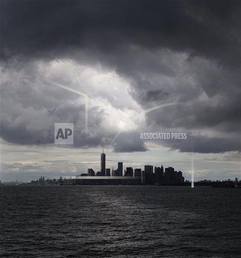 Rain clouds gather over the lower Manhattan skyline, Saturday, Aug. 23, 2014, in New York. (AP Photo/John Minchillo)