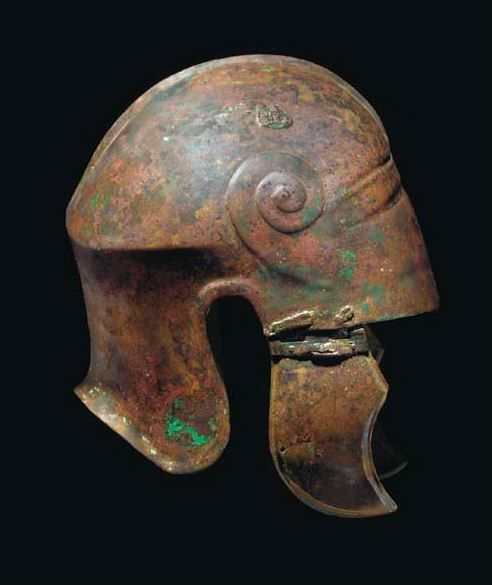 Chalchidian helmet, 5th-4th century B.C. The carinated domed crown with median ridge, a moulded spiral motif on each temple, connected by inverted 'V' mouldings above the brow with traces of engraved detail between, with cusped cheekpieces, 27.6 cm  high. Private collection, from Christie's auction