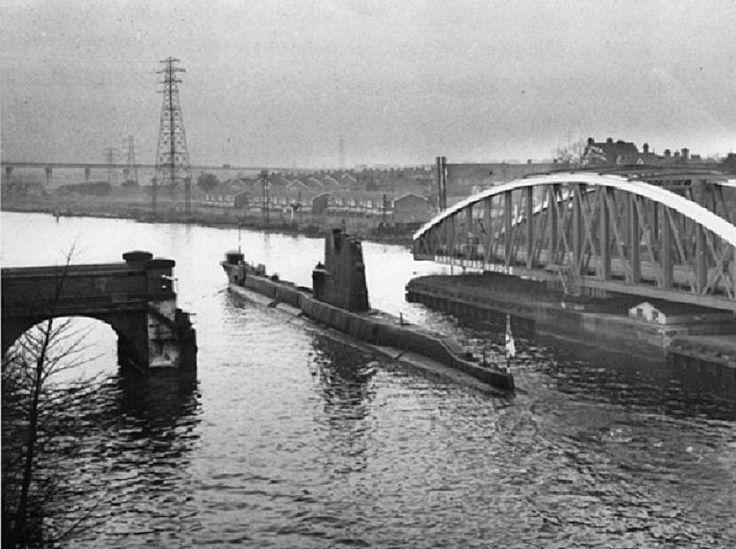Submarine (HMS Tiptoe) passing along canal (out of Salford) passing through swing road bridge at Barton.