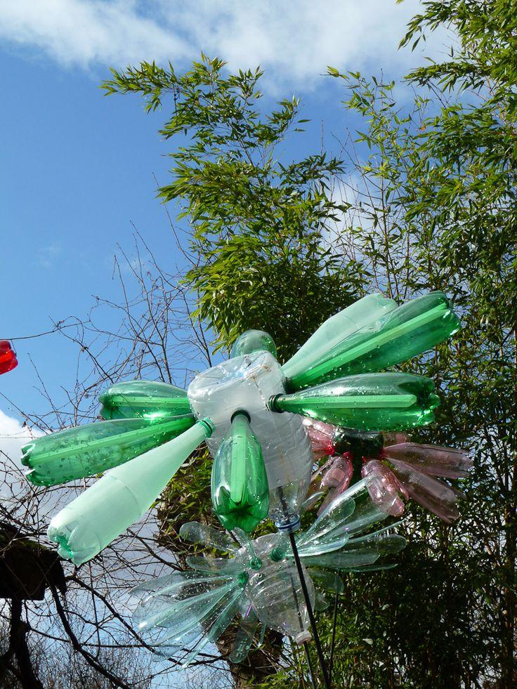 Flowers 2.0, fleurs géantes lumineuses  Flowers 2.0 a été créée par Pierre Estève. C'est une installation lumineuse composée de fleurs géantes réalisées à partir de milliers de bouteilles en plastique multicolores recyclées.  http://www.pariscotejardin.fr/2013/03/flowers-2-0-fleurs-geantes-lumineuses/