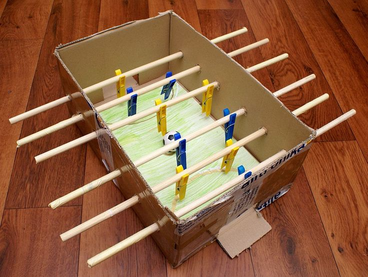 A friend of mine made this low budget soccer game for his kids. It's made of a paper box, a few slats and laundry clips. The grass was painted by his daughter. Only the ball is from a real soccer table.