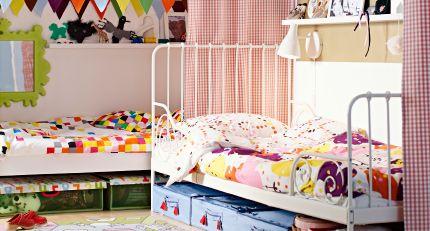 Børneværelse til deling. 2 IKEA senge i L-form med en rumdeler af tekstil imellem.
