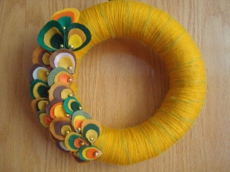 Great take on a yarn wreath. The use of felt oysters is a fantastic alternative to flowers for a funky untraditional edge.  http://sewcraftalicious.wordpress.com/2011/02/10/yarn-wreaths/yarn-wreath-with-felt-oysters/