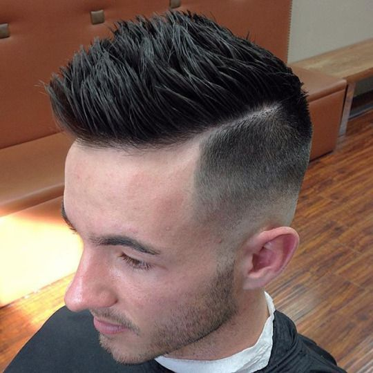 A nice vertically oriented pompadour with a medium skin fade with disconnection.  From: Wake Up and Smell the Barbicide