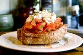 DAKOS is a traditional hard wheat bread soaked in water, olive oil and vinegar, and topped with juicy red tomato, crumbled feta cheese and oregano.
