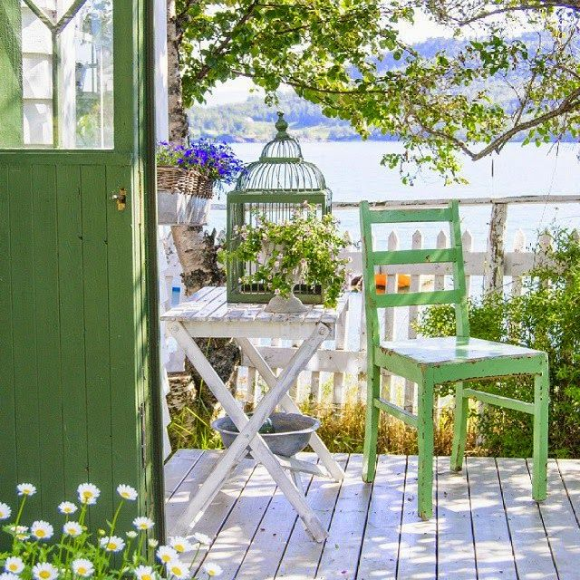 Tranquil. Shaded porch, with charming vintage painted furniture, overlooks water.