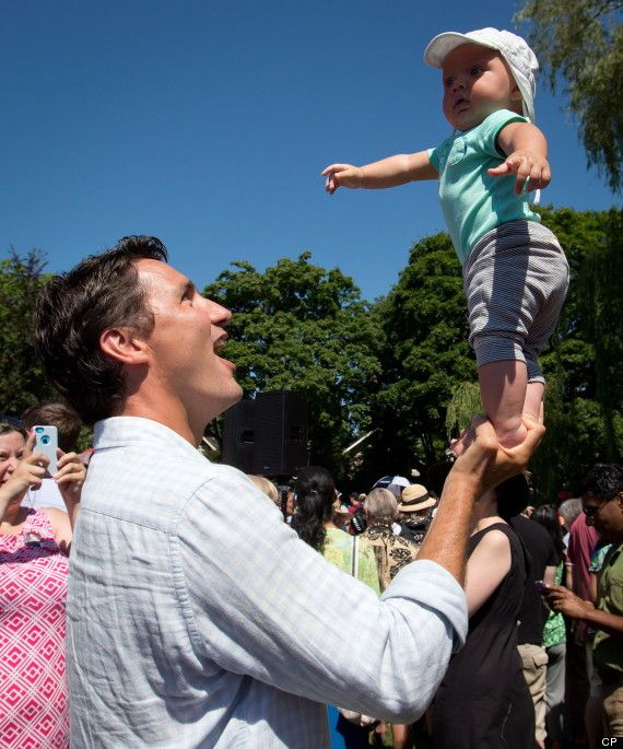 Justin Trudeau balancing his son on one hand