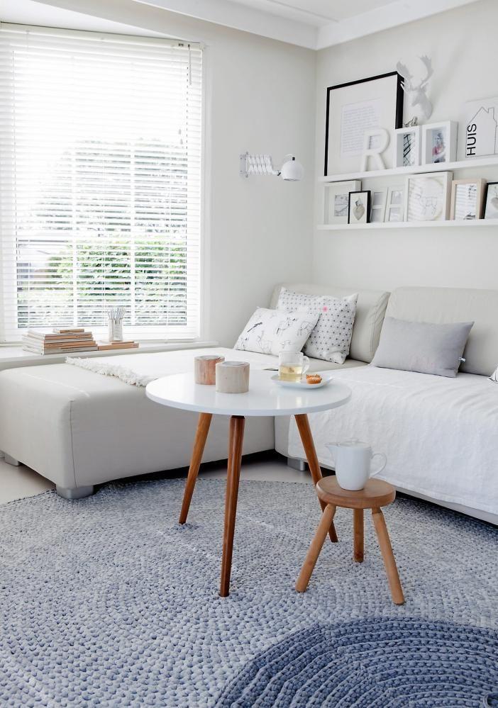 STUE: Interiøret er holdt i hvitt med innslag av tre for å gjøre det varmere. Over sofaen henger mange rammer med fotografier og selvlaget kunst. Putetrekkene er sydd av stoffer fra Ikea.