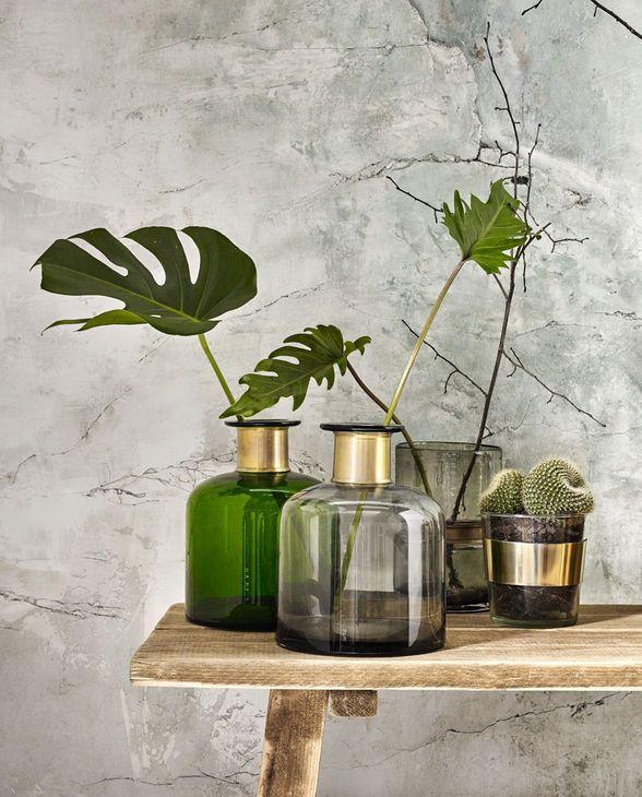 Weiterhin voll im Trend: ein natürlicher Look, wie hier aus Glas, veredelt mit luxuriösem Goldglanz. Die Glasvase des dänischen Design Labels Nordal wird von einem goldfarbenen Eisenring umarmt und setzt so auch schlichteste Zweige effektvoll in Szene.