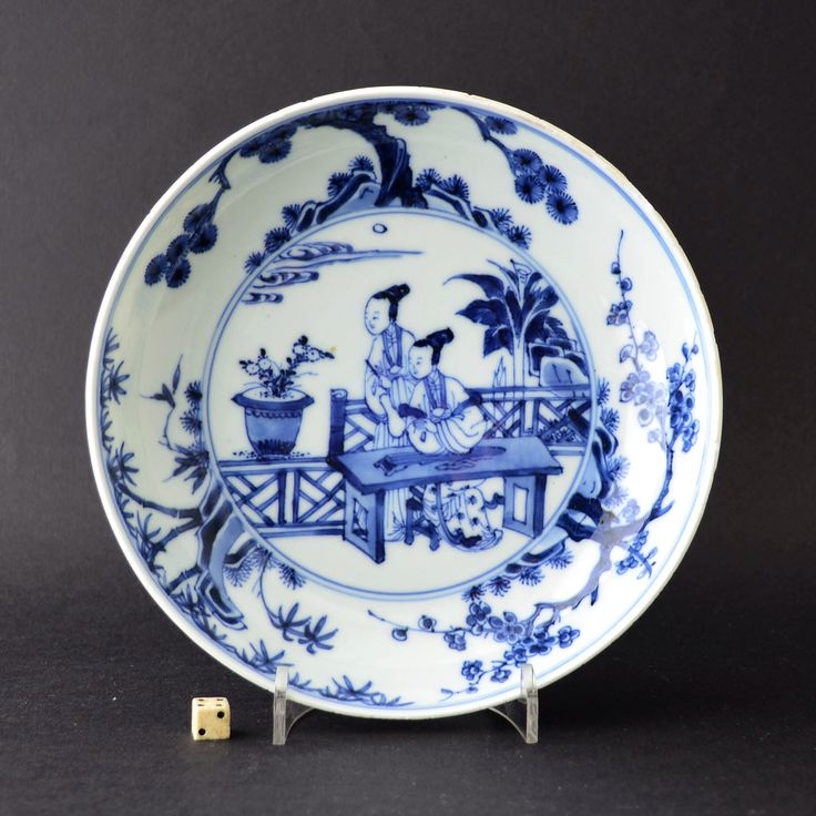 A finely painted 18th century blue and white porcelain dish, Yongzheng period 1723-1735. The centre decorated with two elegant ladies in a garden with a banana plant. They are at a table with a Qin (a lute type instrument). The cavetto with 'The Three Friends of Winter'.