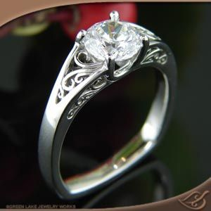 PLATINUM FILIGREE RING   Platinum 4-prong mounting for center 6mm round stone. Ring has top and side face filigree panels, and a squared base.   Custom Portfolio Design - Create Your Own Original! Similar Custom Designs start around $2014.00* (14kt) * Prices do not include center stones unless noted. GREENLAKE JEWELERS