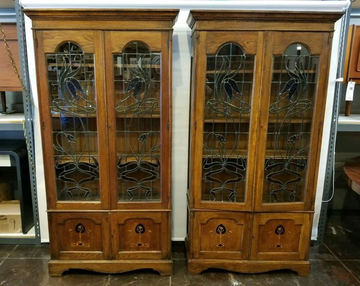 Matching pair oak bookcases with art nouveau detailing. The top doors feature stained glass panels of art nouveau florals in green, blue, yellow, gold, and purple. Both lockable doors swing open to reveal three adjustable thick, solid oak shelves; sturdy enough to hold books or beloved objet. | eBay!
