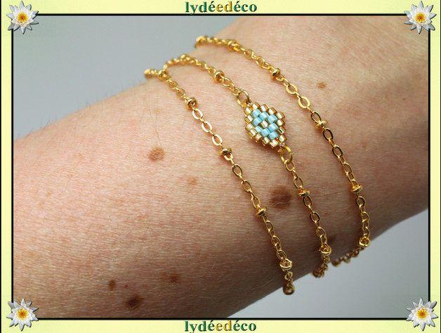 Bracelet plaqué or 18 carats triangle de perles couleurs bleu turquoise et or, tissage à laiguille. Bijou délicat et précieux fait-main par Lydée Déco.  Pendentif losange tissage en perles de verre dimensions 2cm x 0.8cm Fine chaine boule en plaqué or 18K Adapté pour un poignet denviron 17cm (merci de préciser si vous souhaitez une autre taille).  Délicat et raffiné, passionnément fait-main!  ☼Les Bracelets plaqué or tissage de perles sont proposés avec différentes couleurs de perles…