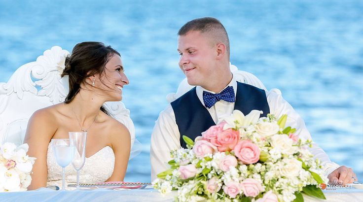 Bride and groom seated in front of the water at their beach wedding reception | Palace Resorts Weddings ®