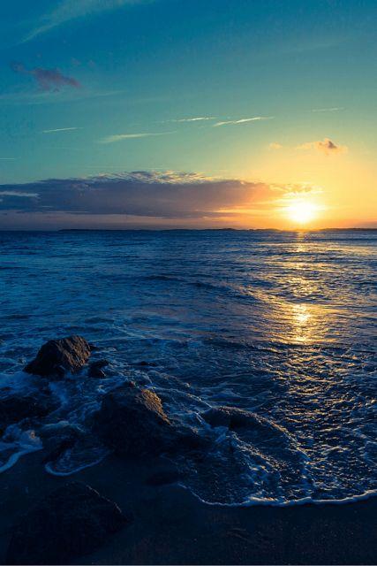 beach at sunrise, rocks on shore...