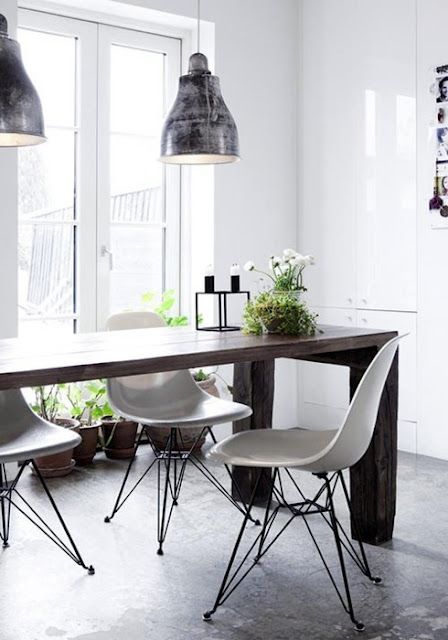 Industrial light fixtures, ultra sleek and modern dining table and to top it off, beautiful classic Eames chairs