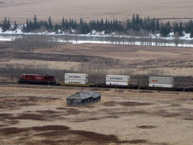 A train passes between the old Glenbow Store and the Bow River at Glenbow Ranch Provincial Park between Cochrane and Calgary, Alberta, Canada.