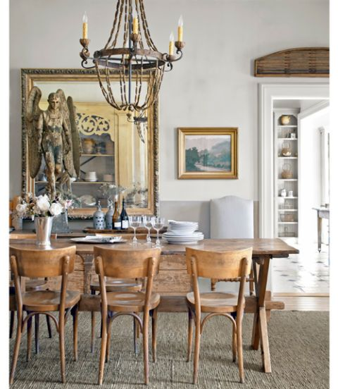 In this California home, the homeowner's favorite possession, an 18th-century wooden angel, looks over the dining room. She nabbed the piece in France, where she also bought the antique pine trestle table, oak bistro chairs, and wood-and-iron chandelier.